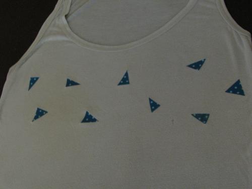 Découpez votre tissu en triangles de différentes tailles, un peu au hasard. Disposez les ensuite sur votre t-shirt et repassez (avec une feuille de papier cuisson entre le tissu et le fer).